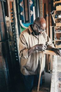Noah Purifoy, founding member of the California Arts Council, which piloted artist-in-the-community outreach programs including in prisons, schools, hospitals and seniors' centers from 1976 until his retirement in 1989, pictured here in his studio in Joshua Tree, CA, circa 2004.